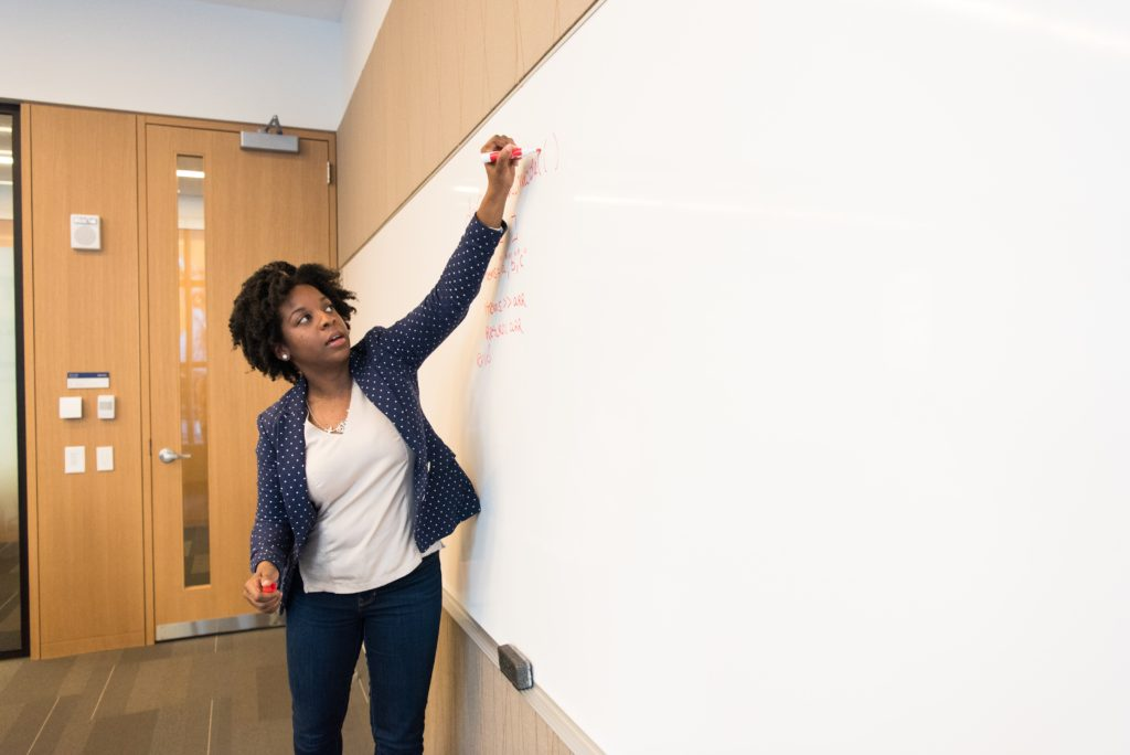 woman-writing-on-dry-erase-board-1181398